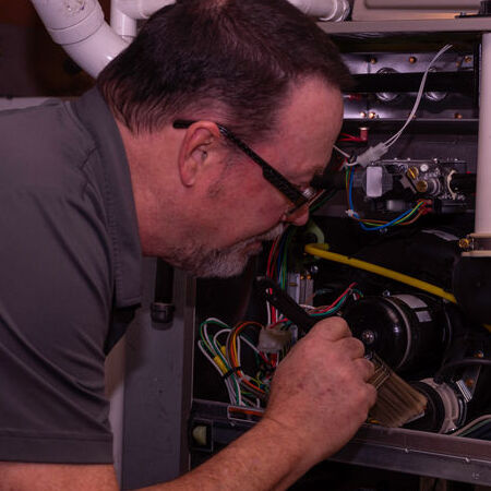 HVAC repairman performing inspection