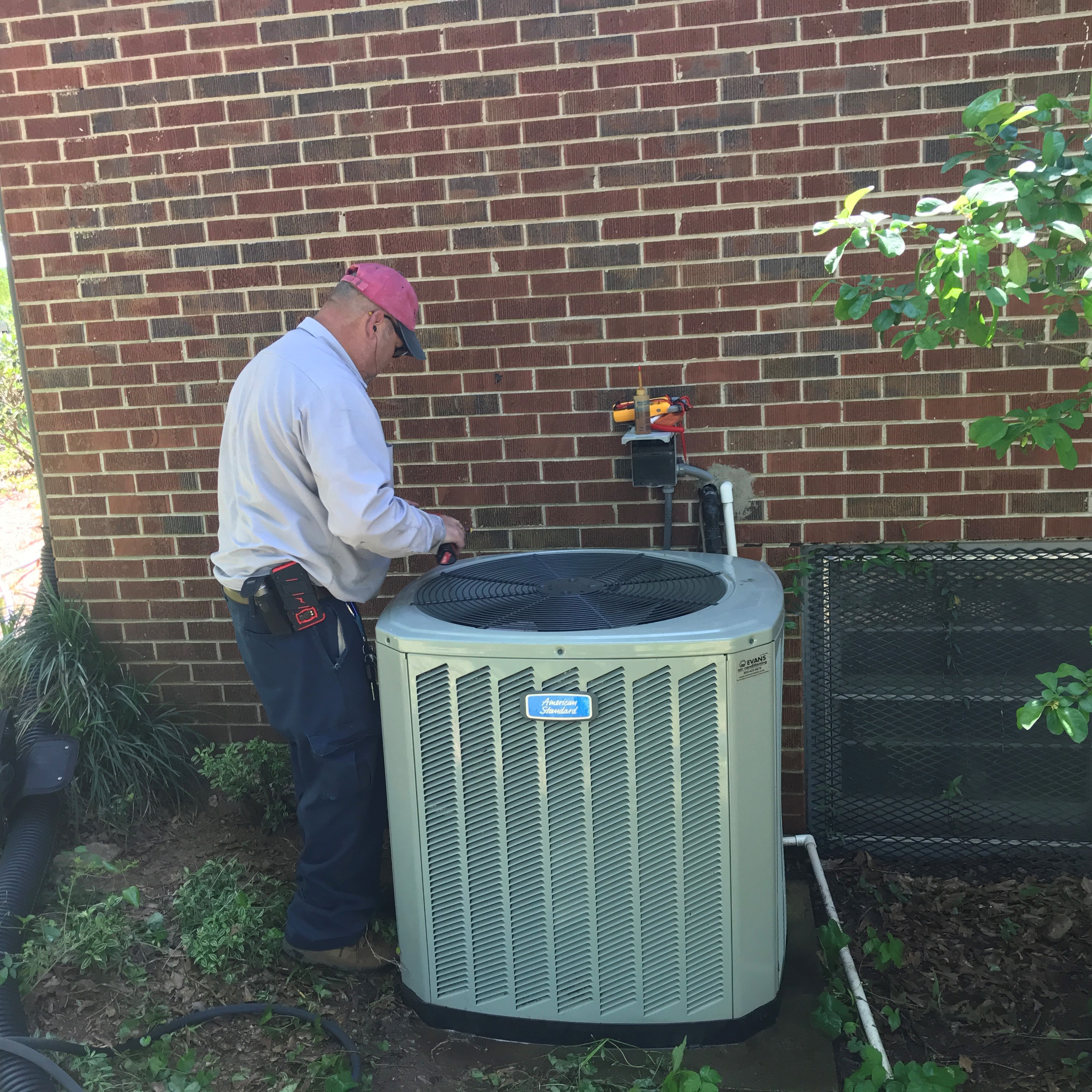 An HVAC Contractor Services an Air Conditioner.